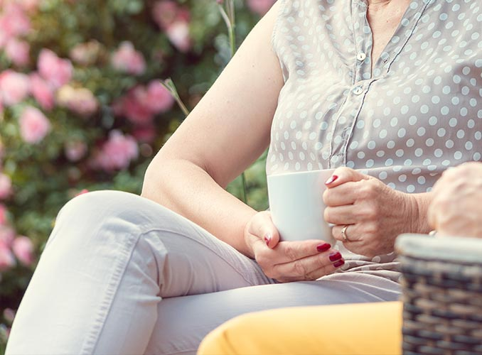 focus on knee - woman enjoying coffee